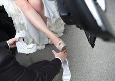 De bruidegom van het liefdehuwelijk helpt de schoenen van de bruidverandering stock fotografie