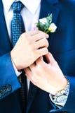 De bruidegom verbetert boutonniere op het jasje royalty-vrije stock afbeeldingen