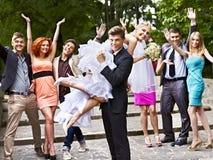De bruidegom vervoert zijn bruid over schouder. Stock Foto