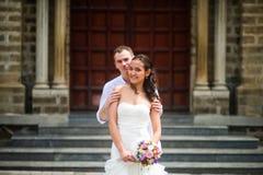 De bruidegom in witte kleren koestert de bruid tegen de achtergrond van de Katholieke Kerk stock foto