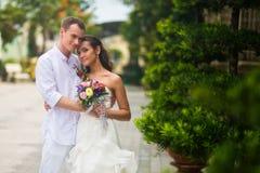 De bruidegom in witte kleren koestert zijn bruid in een mooi Park royalty-vrije stock afbeelding