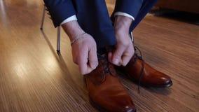 De bruidegom zet op schoenen voor het huwelijk stock video