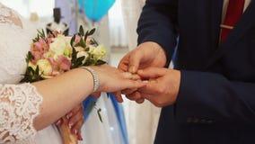 De bruidegom zet de ring op de bruid stock video