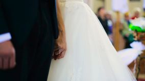 De bruidegom in zwart kostuum houdt de bruid` s hand tenderand belofte zegt stock footage