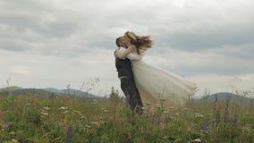 De bruidegomlooppas voor de bruid op een bergheuvels Het Paar van het huwelijk Gelukkige Familie stock video