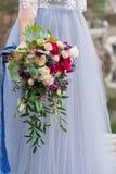 De bruidenhand houdt een huwelijksboeket van rozen en feverweed op de achtergrond van een huwelijkskleding royalty-vrije stock afbeelding