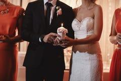 De de bruidgreep en bruidegom houden een familiekaars brandend op de huwelijksdag na de ceremonie Tradities en douane royalty-vrije stock foto