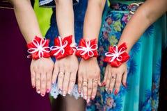 De bruidsmeisjes tonen armbanden op handen Bruid en bruidsmeisjes met bloemarmbanden op handen stock afbeeldingen
