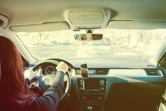 De bruin-haired vrouw drijvend een auto in zonnige dag stock afbeeldingen