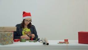 De bruin-haired vrouw snijdt rood lint voor het nieuwe jaar verfraaien in bureau stock videobeelden