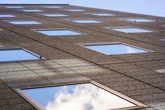 De bruine bureaubouw buiten met vierkante spiegelpatronen die op de hemel en op de wolken wijzen schoot van de bodem stock afbeelding