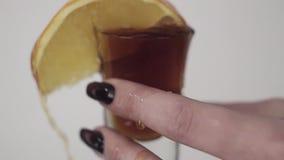 De bruine die vloeistof wordt op glas met citroen gegoten door de hand van de jonge vrouw wordt gehouden stock footage