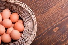 De bruine eieren in een rieten bovenkant van de mand bruine lijst bekijken op het recht Stock Foto's