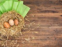 De bruine eieren in hooi nestelen Landelijke ecoachtergrond met bruine kippeneieren en stro op de achtergrond van oude houten pla Stock Foto