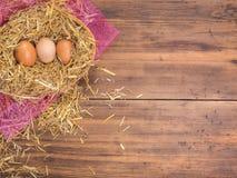 De bruine eieren in hooi nestelen Landelijke ecoachtergrond met bruine kippeneieren en stro op de achtergrond van oude houten pla Royalty-vrije Stock Fotografie