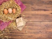 De bruine eieren in hooi nestelen Landelijke ecoachtergrond met bruine kippeneieren en stro op de achtergrond van oude houten pla Royalty-vrije Stock Foto