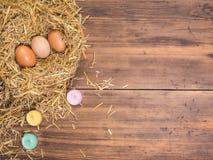 De bruine eieren in hooi nestelen Landelijke ecoachtergrond met bruine kippeneieren, gekleurd kaarsen en stro op de achtergrond v Stock Afbeelding