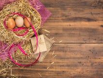 De bruine eieren in hooi nestelen Landelijke ecoachtergrond met bruine kippeneieren, rood lint en stro op de achtergrond van oud Royalty-vrije Stock Foto