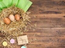 De bruine eieren in hooi nestelen Landelijke ecoachtergrond met bruine kippeneieren, stro, kleurde het giftvakje kaarsen en docum Stock Fotografie