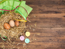 De bruine eieren in hooi nestelen Landelijke ecoachtergrond met bruine kippeneieren, stro, kleurden kaarsen en document op de ach Stock Afbeeldingen