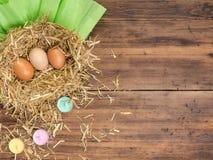 De bruine eieren in hooi nestelen Landelijke ecoachtergrond met bruine kippeneieren, stro, kleurden kaarsen en document op de ach Royalty-vrije Stock Fotografie