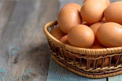 De bruine eieren van de landbouwers kooi-vrije kip in mand, sluiten omhoog, rustieke lijst stock foto