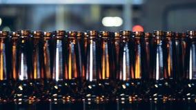 De bruine flessen die zich op een brouwerijtransportband bewegen, sluiten omhoog stock footage