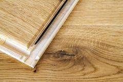 De bruine houten de plankeninstallatie van de parketvloer, sluit omhoog Carpe Stock Foto's