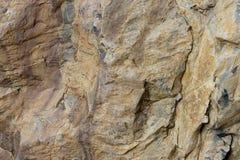 De bruine kleur van de natuursteenhulp Achtergrondrots met een textuur van geel met kleine barsten Doorstane steenlagen van royalty-vrije stock foto's