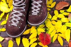 De bruine laarzen van het mensensuède op houten achtergrond met bladeren De herfst of de winterschoenen Royalty-vrije Stock Afbeeldingen