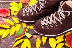 De bruine laarzen van het mensensuède op houten achtergrond met bladeren De herfst of de winterschoenen Royalty-vrije Stock Foto's