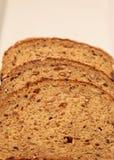 De bruine plakken van het multigrainbrood op een witte plaat Royalty-vrije Stock Fotografie