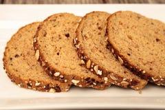 De bruine plakken van het multigrainbrood op een witte plaat Stock Foto
