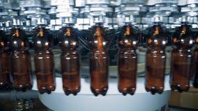 De bruine plastic die flessen worden met bier worden gevuld terwijl zich rond het bewegen stock videobeelden