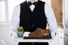 De Bruine Schoenen van Butler Carrying Pair Of royalty-vrije stock foto