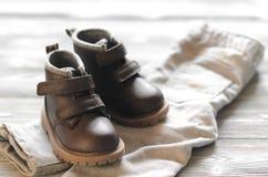 De bruine schoenen van leerjonge geitjes en denimbroek op houten achtergrond Stock Afbeeldingen