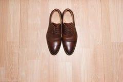 De bruine schoenen van leermensen op houten grond, boven schot Royalty-vrije Stock Foto