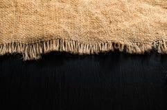 De bruine textuur van de stoffenjute op donkere houten lijst Stock Afbeeldingen