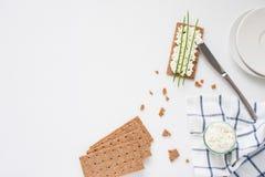 De bruine Zweedse crackers van het rogge knapperige brood met uitgespreide die kwark, met dunne groene ui, op stuk van doek wordt Stock Foto