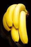 De brunch van bananen op glaslijst. Geïsoleerd_ op zwarte. Stock Foto's