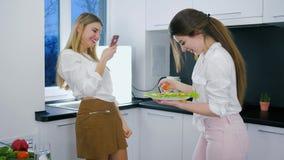 De brunch van gelukkige meisjes met in hand voedsel maakt video op androïde bij keuken stock video
