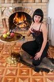De brunette en een brandende open haard. Royalty-vrije Stock Foto's