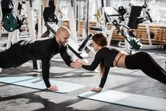 De brutale atletische mens en het jonge slanke meisje gekleed in zwarte soortenkleren doen hand in hand plankholding in royalty-vrije stock afbeelding