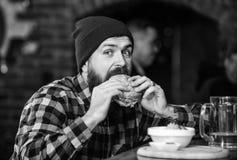De brutale hipster gebaarde mens zit bij barteller Hoog Calorievoedsel Bedrieg maaltijd Heerlijk hamburgerconcept Geniet van smaa royalty-vrije stock fotografie