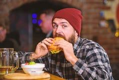 De brutale hipster gebaarde mens zit bij barteller Hoog Calorievoedsel Bedrieg maaltijd Heerlijk hamburgerconcept Geniet van smaa stock fotografie