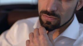 De brutale man streek zijn baardhand, close-up stock videobeelden