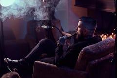 De brutale mens maakt aardige nevelige damp terwijl het ontspannen dichtbij open haard en rokende waterpijp royalty-vrije stock foto