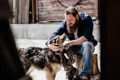 De brutale mens met een baard gekleed in vrijetijdskleding zit op een stomp en petting een hond naast de houten muur stock afbeeldingen