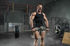 De brutale sterke atletische treinen van de mensenbodybuilder in de gymnastiek Stock Afbeelding