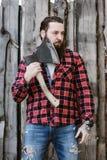 De brutale sterke mens met een baard kleedde zich in een gecontroleerd overhemd en gescheurde jeans die zich met een bijl in de h royalty-vrije stock afbeelding